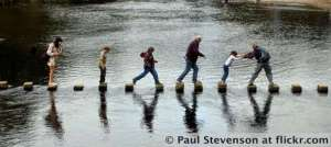 A-Family-Crossing-Stepping-Stones-On-A-River